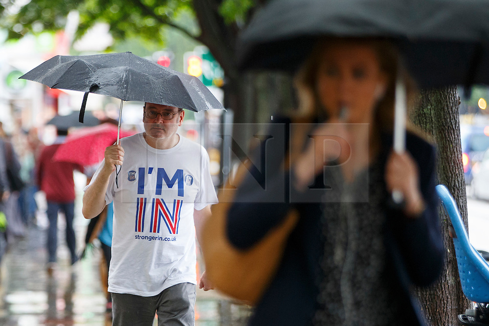 © Licensed to London News Pictures. 23/06/2016. London, UK. A Stronger In campaigner takes shelter from the rain underneath his umbrella in Islington, London on the polling day of the EU referendum on 23 June 2016. Photo credit: Tolga Akmen/LNP
