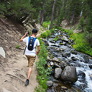A young man hikes in the Eastern Sierras near Mammoth Lakes, CA on his way to Emerald Lake.