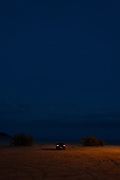 Car with rear lights illuminated parked on beach on Costa Brava, Spain.