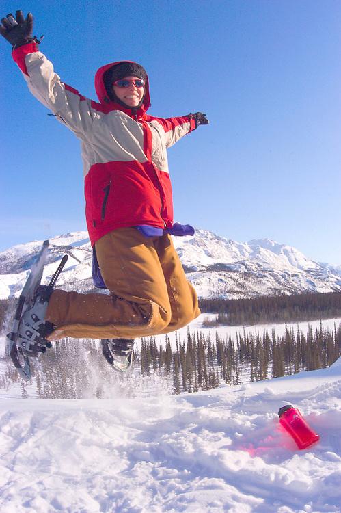 Alaska , Brooks Range. Iniakuk Lake Lodge. A jubuliant snow shoe enthusiast leaps for joy in March at the Iniakuk lake Lodge.
