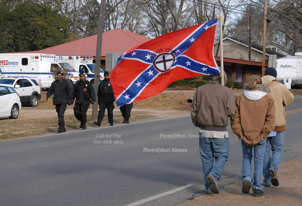 """A group of white supremits carrying a flag that read """" white power -knights of the ku klux klan"""" walk by a group of Black Panthers after a rally on Martin Luther King Day in Jena Louisiana Jan, 21, 2008. A group of protesters march to Jena High School on the Martin Luther King Jr. holiday in Jena, La., Monday, Jan. 21, 2008. The protest was organized by the self-described 'pro-majority' Nationalist Movement of Learned, Mississippi, lead by Richard Barrett, and was being held in opposition to the six black teenagers who were arrested in the beating of a white classmate in December 2006, and the King holiday. The protest drew about 50 participants and 100 counter-demonstrators to Jena.(Photo/© Suzi Altman) The Rankin County Sheriff's Department has confirmed that the body of white supremacist and attorney Richard Barrett, 67, was found in his Pearl home today, apparently the victim of a homicide."""