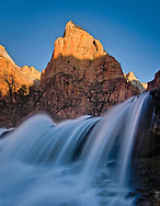 First light hit's the peak of Isaac, one of the three Patriarchs in Zion above a small waterfall in the virgin river