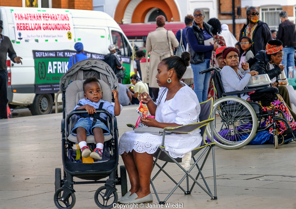Woman feeding her child at Reparations Revolution event on Afrikan Emancipation Day in Windrush Square, Brixton 2021.
