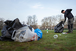 © Licensed to London News Pictures. 31/03/2021. London, UK. A worker collects rubbish in Greenwich Park after hundreds of people visited the park to enjoy sunny weather and take advantage of new lockdown rules that allow groups of six to meet outside. Photo credit: George Cracknell Wright/LNP