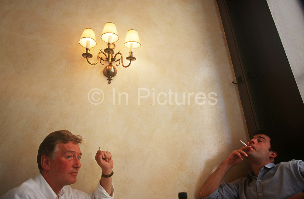 Two men smoke cigarettes in a London restaurant in the era of public, indoor smoking. The two friends have finished their long lunch and sit back to enjoy the after meal experience of inhaling the smoke, their faces showing the pleasures of an otherwise addiction to the tobacco filled cigarette. This is the upside though and The smoking ban came into effect  in England on 1st July 2007; in Scotland on 26 March 2006; in Wales on 2 April 2007 and in Northern Ireland on 30 April 2007. But publicans and breweries reported a drop in sales to the smoking ban, their lowest level since the 1930s.