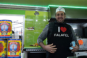 Falafel seller wearing his I love falafel apron in his kiosk in the city centre on 18th January 2020 in Birmingham, United Kingdom. Falafel is a deep-fried ball or patty made from ground chickpeas, fava beans, or both and is a traditional Middle Eastern food, commonly served in a pita, which acts as a pocket, or wrapped in a flatbread.