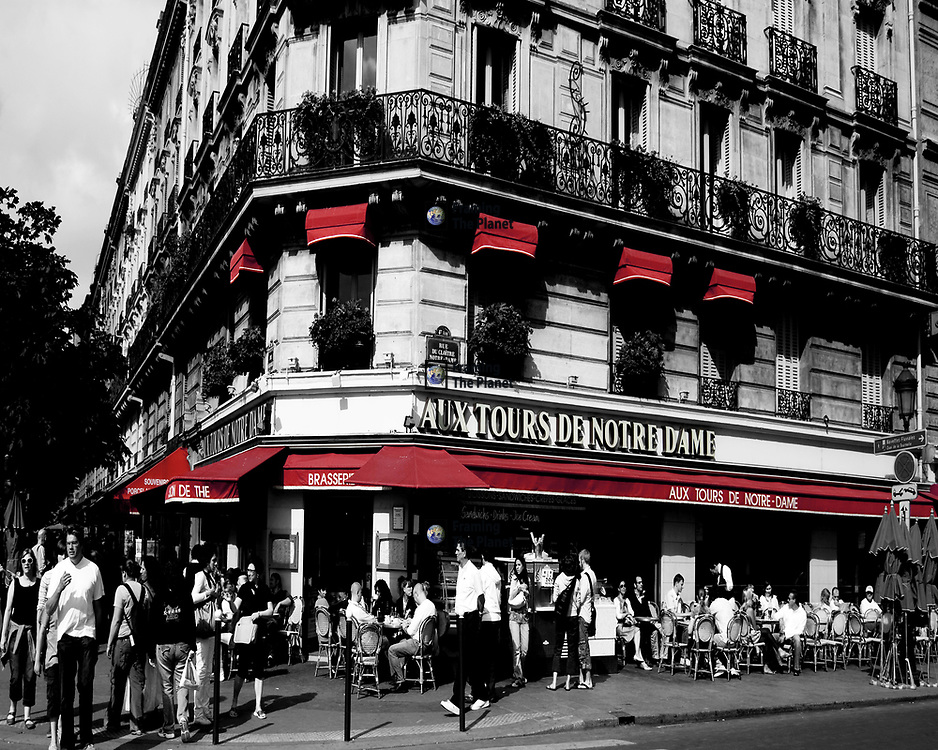 Café en Paris, this black and white colour isolation image shows us one of the many famous cafés of Paris. This particular café is near the ancient cathedral of Notre Damn in this historic area of the city. We see plenty of passers by as well as patrons of the café. ..This is a classic old French Café scene photograph taken in the heart of the city showing that this way of life is still alive and wheel. There are many street corners in the capitol of France where you can find Parisians enjoying a coffee, usually a café crème out in the pavement or the side of the street