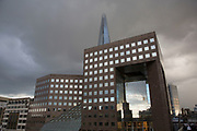 The Shard looming over the Price Waterhouse Coopers building on cloudy and stormy day in London, UK.  The Shard, also referred to as the Shard of Glass, Shard London Bridge and formerly London Bridge Tower, is an 87-storey skyscraper in London that forms part of the London Bridge Quarter development.