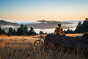Mountain biker enjoying a summer evening ride as fog rolls into Sonoma County's coastal valleys from the Pacific Ocean.
