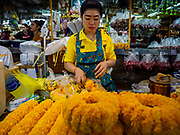 27 FEBRUARY 2019 - BANGKOK, THAILAND: A woman in Pak Klong Talat, Bangkok's flower market, makes marigold garlands in the market. Bangkok, a city of about 14 million, is famous for its raucous nightlife. But Bangkok's real nightlife is seen in its markets and street stalls, many of which are open through the night.        PHOTO BY JACK KURTZ