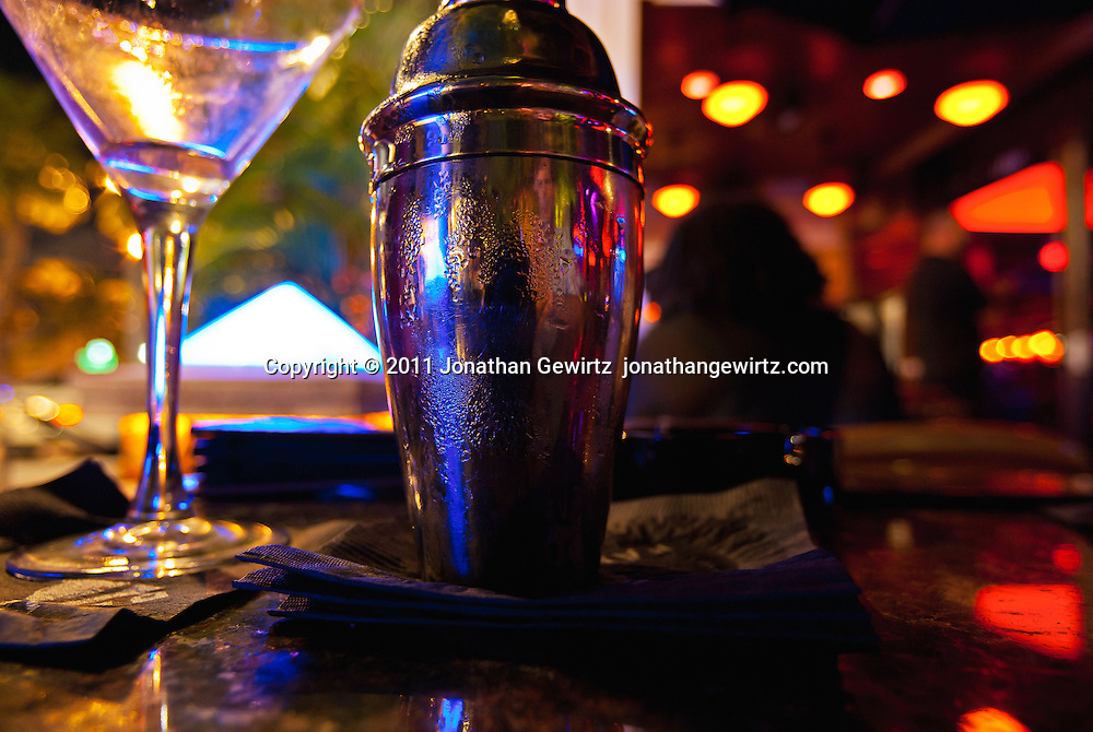 A stainless steel cocktail shaker and drink glass on a restaurant table under subdued colorful light. WATERMARKS WILL NOT APPEAR ON PRINTS OR LICENSED IMAGES.
