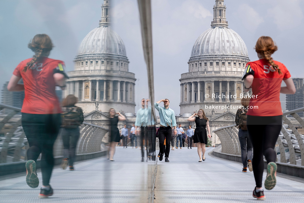 With the dome of St Paul's cathedral in the distance, a runner and pedestrians cross the river Thames on the Millennium Bridge, on 24th June 2021, in London, England. London's newest river crossing for 100-plus years coincided with the Millennium. It was hurriedly finished and opened to the public on 10 June 2000 when an estimated 100,000 people crossed it to discover the structure oscillated so much that it was forced to close 2 days later. Over the next 18 months designers added dampeners to stop its wobble but it already symbolised what was embarrassing and failing in British pride. Now the British Standard code of bridge loading has been updated to cover the swaying phenomenon, referred to as 'Synchronous Lateral Excitation'. (Photo by Richard Baker / In Pictures via Getty Images) CREDIT RICHARD BAKER.