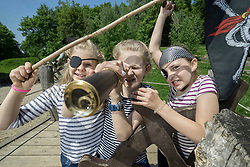 Three girls playing on a pirate ship in adventure playground, Bavaria, Germany