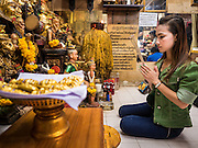 "25 MAY 2015 - BANGKOK, THAILAND:  AUEN, who sells cosmetics, prays before getting a Sak Yant tattoo. She said she was hoping the tattoo would help her business. Sak Yant (Thai for ""tattoos of mystical drawings"" sak=tattoo, yantra=mystical drawing) tattoos are popular throughout Thailand, Cambodia, Laos and Myanmar. The tattoos are believed to impart magical powers to the people who have them. People get the tattoos to address specific needs. For example, a business person would get a tattoo to make his business successful, and a soldier would get a tattoo to help him in battle. The tattoos are blessed by monks or people who have magical powers. Ajarn Neng, a revered tattoo master in Bangkok, uses stainless steel needles to tattoo, other tattoo masters use bamboo needles. The tattoos are growing in popularity with tourists, but Thai religious leaders try to discourage tattoo masters from giving tourists tattoos for ornamental reasons.       PHOTO BY JACK KURTZ"