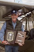 L-4J owner with his awards from Airventure 2019 and his L-4 at Warbirds Over the West.