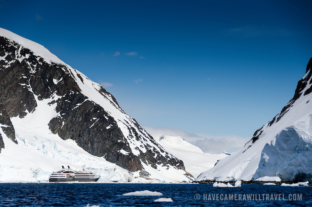 A large luxury French cruise ship, the L'Austral, heads through a narrow channel between mountains on the Antarctic Peninsula (left) and Cuverville Island (right).