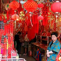 Asia, China; Shanghai. Chinese lanterns and shopkeeper.