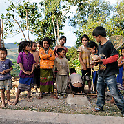 Village children in Luang Namtha province in northern Laos. The boy in the foreground with the black shirt is holding a spinning top wrapped with string.