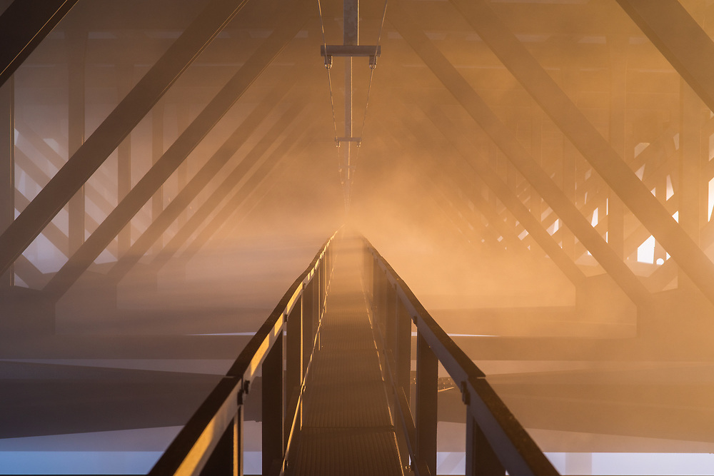 Fog and morning light sweep through the beams underneath the New River Gorge Bridge in West Virginia.