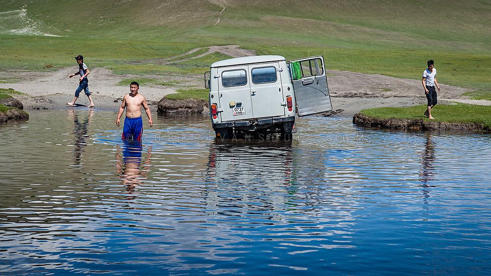 Three men exit a Russian van stranded during a river crossing in Khovsol province, Mongolia. Photo © Robert van Sluis