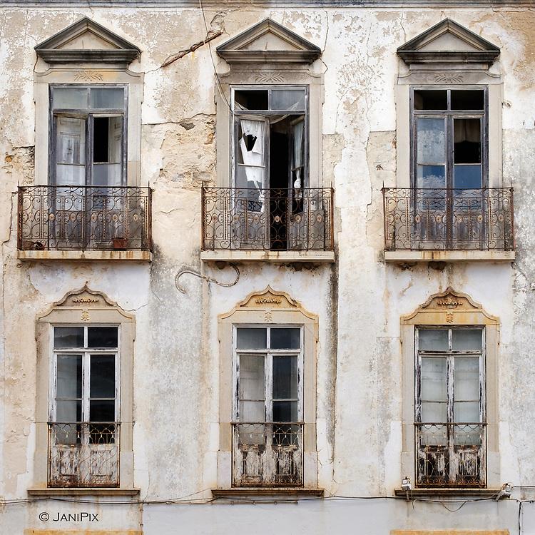 Balcony windows in a narrow street in Tavira, Algarve, Portugal