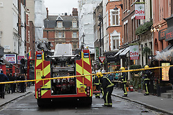 © Licensed to London News Pictures. 23/12/2014. London, UK. Fire engines and fire officers attend to a fire at The Delhi Brasserie, an Indian restaurant in Frith Street, Westminster, London this afternoon. The fire is believed to have started in the extractor fan system in the restaurant and has now been extinguished. Photo credit : Vickie Flores/LNP