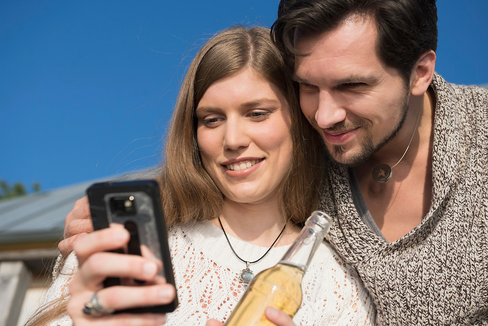 Close up couple cell phone SMS drinking beer
