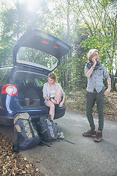Young couple preparing for hiking in a forest, Bavaria, Germany