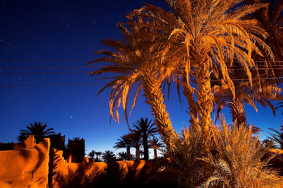 Adobe walls, palm trees and power lines are lit by street lights at twilight along a dirt road leading to Ait Bounou, an ancient village in the Moroccan Sahara on November 8, 2007. Ait Bounou is threatened by extreme drought, yet the path is lined with newly built luxury tourist hotels equipped with swimming pools.