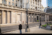 A man waits on the street in front of the Bank of England in what would normally be the morning rush hour in the City of London on March 17th, 2020. The financial district of the UK is unusually quiet after the government requested people to refrain from all but essential travel and activities yesterday.