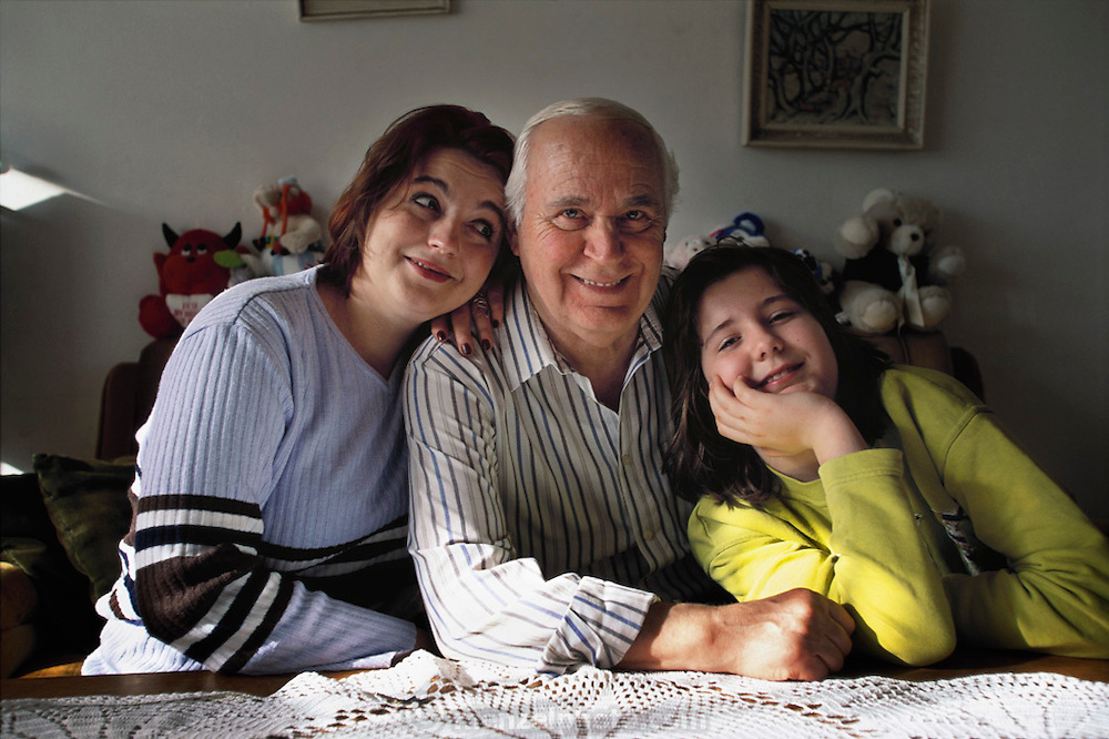 Portrait of Lokman Demirovic (father of Arina and grandfather of Nadja); Nadja Bucolovic (10, daughter of Arina); and Arina Bucolovic (mother of Nadja and daughter of Lokman) in the living room of their Sarjevo apartment. From coverage of revisit to Material World Project family in Sarajevo, Bosnia & Herzegovina, 2001. ©2005 Hungry Planet: What the World Eats