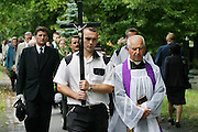 Priest leading funeral procession of Henryk Nowicki in Powazek Cemetery, Warsaw Poland.