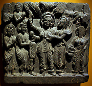 Birth of the Buddha.  Gandhara, about AD 200.  Schist.  Standing in a grove, Queen Maya gives birth to Prince Siddhartha Cautama, the future Buddha, from her right-side.  The infant is received by the god Indra, while other deities stand in attendance.