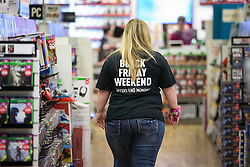 """© Licensed to London News Pictures . 27/11/2015 . Manchester , UK . A member of staff wearing a """" Black Friday Weekend """" t-shirt at a branch of Game in Cheetham Hill in North Manchester this morning (Friday 27th November) . Last year (2014) scuffles and fights were reported amongst queuing bargain-hunters . Photo credit: Joel Goodman/LNP"""