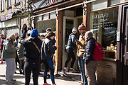 Daily life continues but not as as normal with some rules and restrictions in Hackney on 21st March 2020 in London, United Kingdom. Broadway market on a Saturday morning, queue at Climpsons coffee shop.