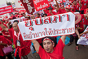 """Mar. 26, 2009 -- BANGKOK, THAILAND: People hold up signs at a protest of Red Shirts in Bangkok Thursday. More than 30,000 members of the United Front of Democracy Against Dictatorship (UDD), also known as the """"Red Shirts""""  and their supporters descended on central Bangkok Thursday to protest against and demand the resignation of current Thai Prime Minister Abhisit Vejjajiva and his government. Abhisit was not at Government House Thursday. The protest is a continuation of protests the Red Shirts have been holding across Thailand in March.  Photo by Jack Kurtz"""