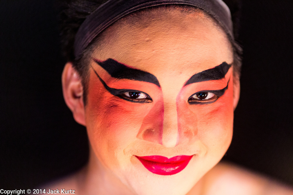 """28 JANUARY 2014 - BANGKOK, THAILAND: A performer with the Tear Kia Ee Lye Heng opera troupe before a show. They were performing for a business in the Min Buri district of Bangkok for the Lunar New Year, which this year is Jan 31. Chinese opera was once very popular in Thailand, where it is called """"Ngiew."""" It is usually performed in the Teochew language. Millions of Teochew speaking Chinese emigrated to Thailand (then Siam) in the 18th and 19th centuries and brought their cultural practices with them. Recently the popularity of ngiew has faded as people turn to performances of opera on DVD or movies. There are still as many 30 Chinese opera troupes left in Bangkok and its environs. They are especially busy during Chinese New Year when they travel from Chinese temple to Chinese temple performing on stages they put up in streets near the temple, sometimes sleeping on hammocks they sling under their stage. They are also frequently hired by Chinese owned businesses to perform as a form of merit making.    PHOTO BY JACK KURTZ"""