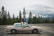 David Balatero sits on the roof of his old Buick in an empty parking lot after a day of snowboarding on Blackcomb Mountain in Whistler, British Columbia, Canada on April 4, 2005.