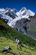 """A trekker ascends steep terrain below glaciers flowing from Yerupaja Grande (right, west face, 6635 m or 21,768 ft), the second-highest peak in Peru, highest in Cordillera Huayhuash, and highest point in the Amazon River watershed (which is on the other side of the mountain). At left is Mount Jirishanca, or the """"Icy Beak of the Hummingbird"""" (6126 m or 20,098 feet elevation) in the Andes Mountains, Peru, South America. We trekked from here on the Pacific side around to the Amazon River watershed side."""