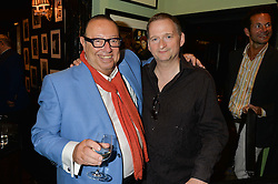 Left to right, LAURENCE ISAACSON and writer, actor and director JONATHAN MOORE at a Bastille Day Cocktail Party at L'Escargot, 48 Greek Street, London on 14th July 2014.