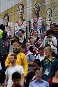 With giant presence of Team GB role-model athlete heroes behind them, spectator crowds descend steps at the Westfield City shopping complex, Stratford that leads to the Olympic Park during the London 2012 Olympics, the 30th Olympiad. The ad is for sports footwear brand Adidas and their 'Take the Stage' campaign including diver Tom Daley, gymnast Louis Smith and the darling of British athletics, heptathlete gold medallist Jessica Ennis. Situated on the fringe of the 2012 Olympic park, Westfield is Europe's largest urban shopping centre providing the main access to the Olympic park with a central 'street' giving 75% of Olympic visitors access to the main stadium so retail space.