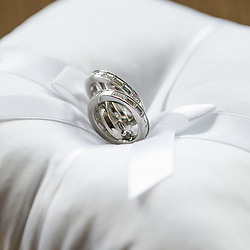silver wedding rings on a silk pillow