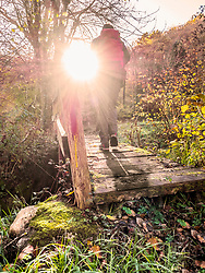 Man crossing a wooden bridge during a hiking tour in the Picos de Europa near the village of Potes, Cantabria, Spain