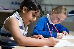 Two girls sitting at desk in classroom working on maths problems,
