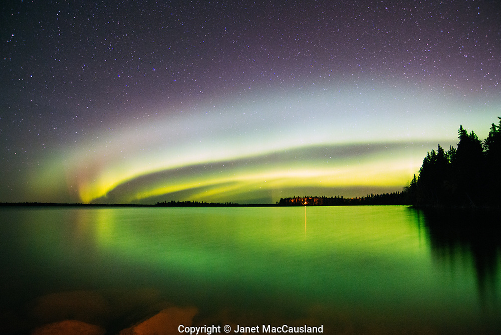 In Saskatchewan, Canada, the Aurora Borealis shows its polarized circular magnetic field in a series of arcs of green, luminous light.