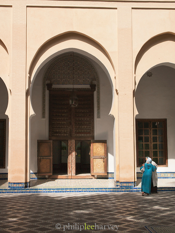 Two women greet each other in the Dar Batha Museum in Fes, Morocco