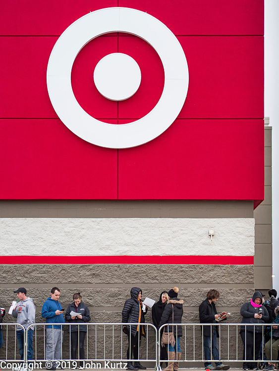 """28 NOVEMBER 2019 - ANKENY, IOWA: People line up at the Target store in Ankeny, Iowa, Thursday. """"Black Friday"""" is the unofficial start of the Christmas holiday shopping season and has traditionally thought to be one of the busiest shopping days of the year. Brick and mortar retailers, like Target, are facing increased pressure from online retailers this year. Many retailers have started opening on Thanksgiving Day. Target stores across the country opened at 5PM on Thanksgiving to attract shoppers with early """"Black Friday"""" specials.          PHOTO BY JACK KURTZ"""