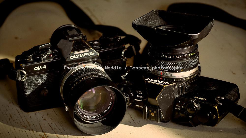 London, England - February 23, 2021: Two Olympus 35mm film single lens reflex cameras sitting on a Billingham 550 camera bag