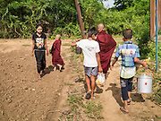 25 MAY 2013 - MAE SOT, TAK, THAILAND:  A Burmese woman passes a Burmese monk leading novices through the forest during their morning alms rounds through an unofficial village of Burmese refugees north of Mae Sot, Thailand. They live on a narrow strip of land about 200 meters deep and 400 meters long that juts into Thailand. The land is technically Burma but it is on the Thai side of the Moei River, which marks most of the border in this part of Thailand. The refugees, a mix of Buddhists and Christians, settled on the land years ago to avoid strife in Myanmar (Burma). For all practical purposes they live in Thailand. They shop in Thai markets and see their produce to Thai buyers. About 200 people live in thatched huts spread throughout the community. They're close enough to Mae Sot that some can work in town and Burmese merchants from Mae Sot come out to their village to do business with them.   PHOTO BY JACK KURTZ