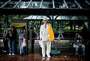 """Duke of the Realm Richard """"Dick"""" B. Clifton, a member of the Royal Rosarians, ambassadors of goodwill for the city of Portland, Ore., waited for a light rail train in the rain after the city's Rose Parade in June."""